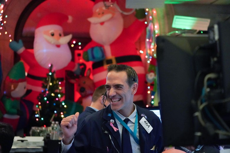 A trader pumps his fist at the closing bell of the New York Stock Exchange on Dec. 5. Inflatable Santas and other Christmas decorations are in the background.