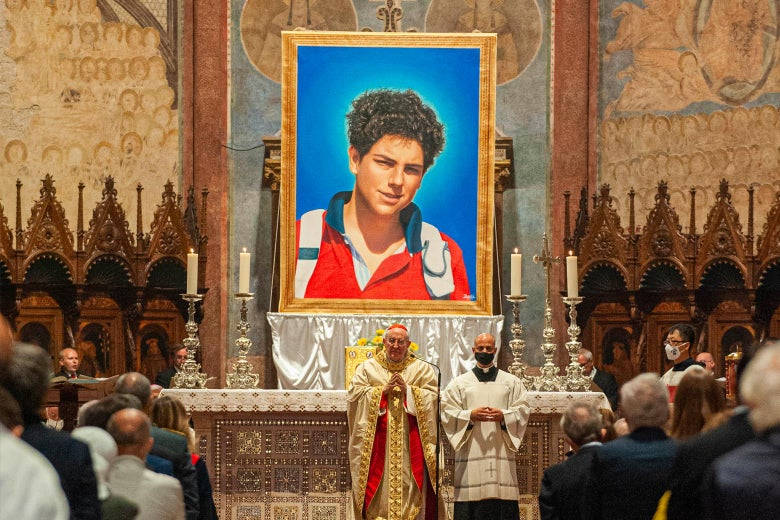 A cardinal and priest stand beneath a portrait of the 15-year-old Carlo Acutis.