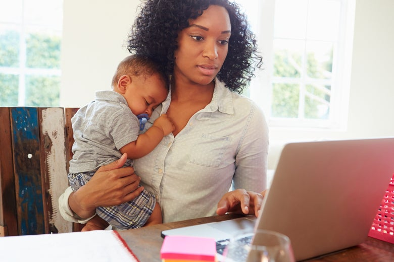A woman holds a baby while working at her laptop.