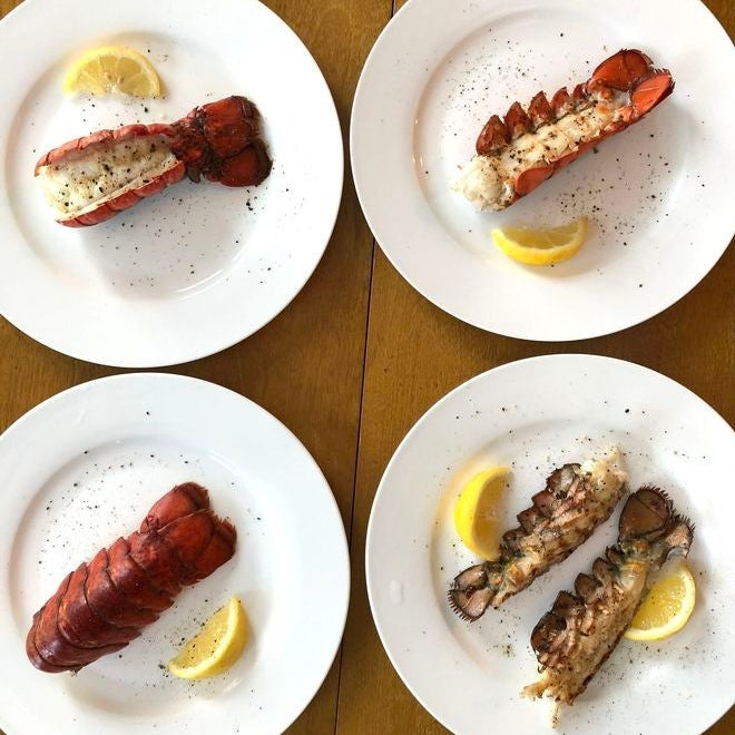 Lobster tails, cooked in different styles, with lemon wedges on four separate plates.