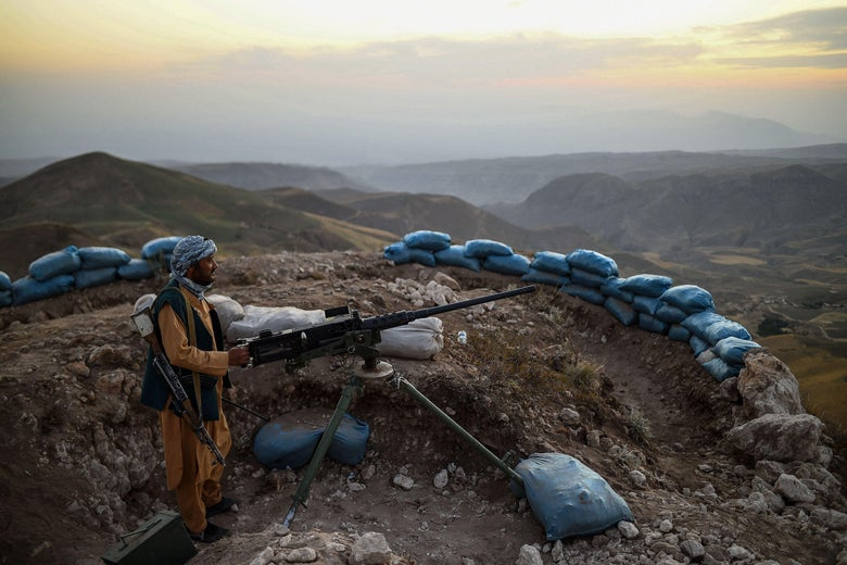 A man operates a gun mounted on a tripod on a rocky outcropping