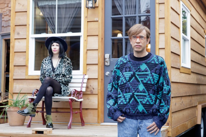 Carrie Brownstein (left) and Fred Armisen (right) stand morosely in character for Portlandia. Armisen wears a tragic, baggy hipster sweater and Brownstein is decked out in a wide-brim hat and cheetah-print wrap dress.