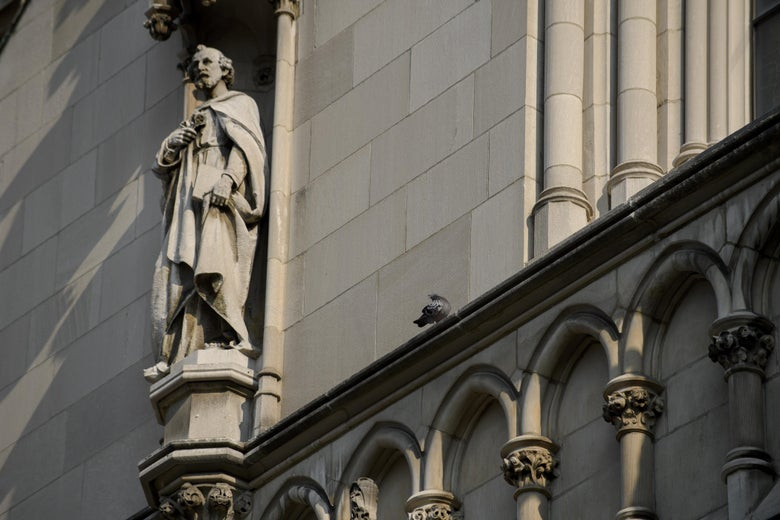 A shot of the side of St. Paul Cathedral, with a sculpture of a figure praying.