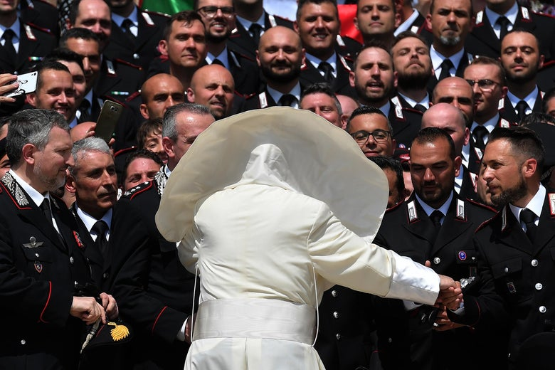 Pope Francis, seen from behind with his cape billowing in the wind, greets a large group of uniformed Carabinieri.