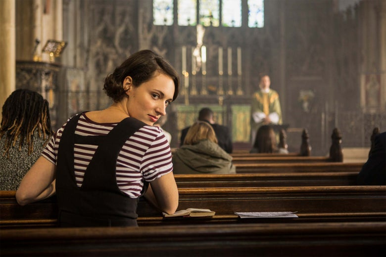 In this still from Fleabag, Phoebe Waller-Bridge breaks the fourth wall by staring directly into the camera while sitting in a church pew.