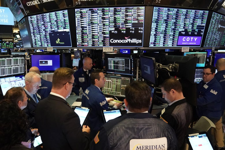 Traders hold tablets as they look up at a bunch of screens.