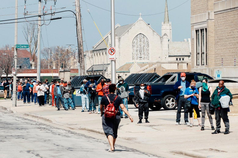 Long line of people wrapped around a street corner in Milwaukee.