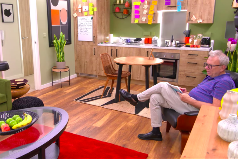 A man in a blue shirt, khaki pants, and black shoes sits on a chair in the corner of a room. There are wood kitchen cabinets and a wood small table behind him; in front of him is a red rug and lime green couch. A coffee table is on the rug and has a bowl of fruit on it.