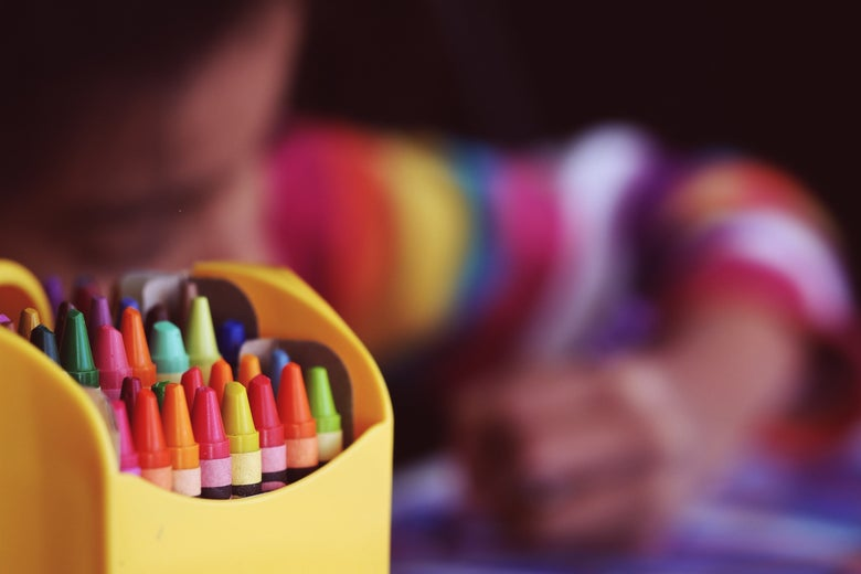 A box of crayons in focus, with a blurred child drawing in the background
