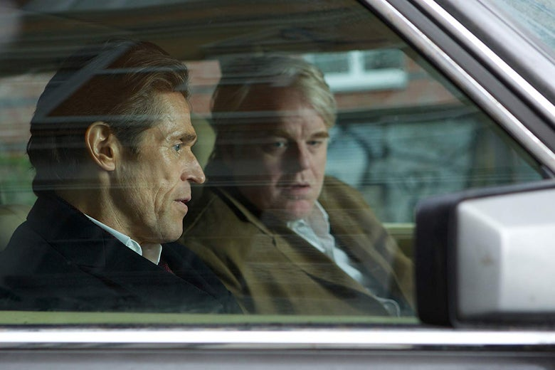 Willem Dafoe and Phillip Seymour Hoffman sit in a car.