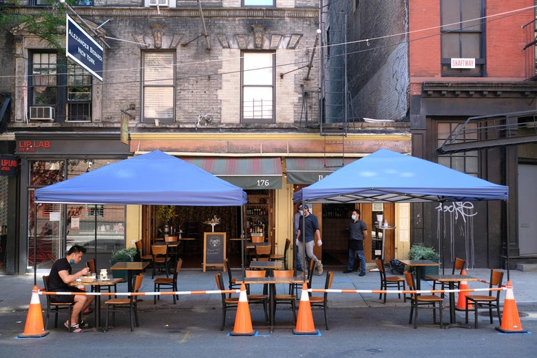 A person sits a table under a canopy placed outside a restaurant.