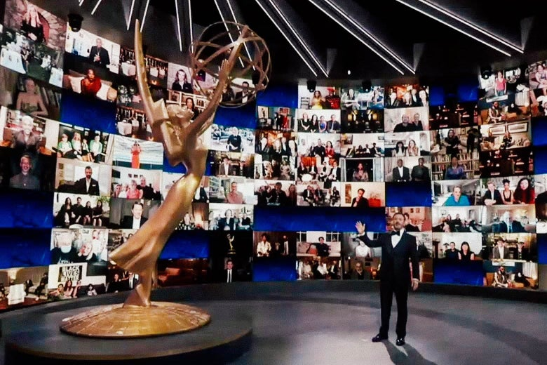 Jimmy Kimmel next to a large Emmys statuette and in front of Zoom screens.