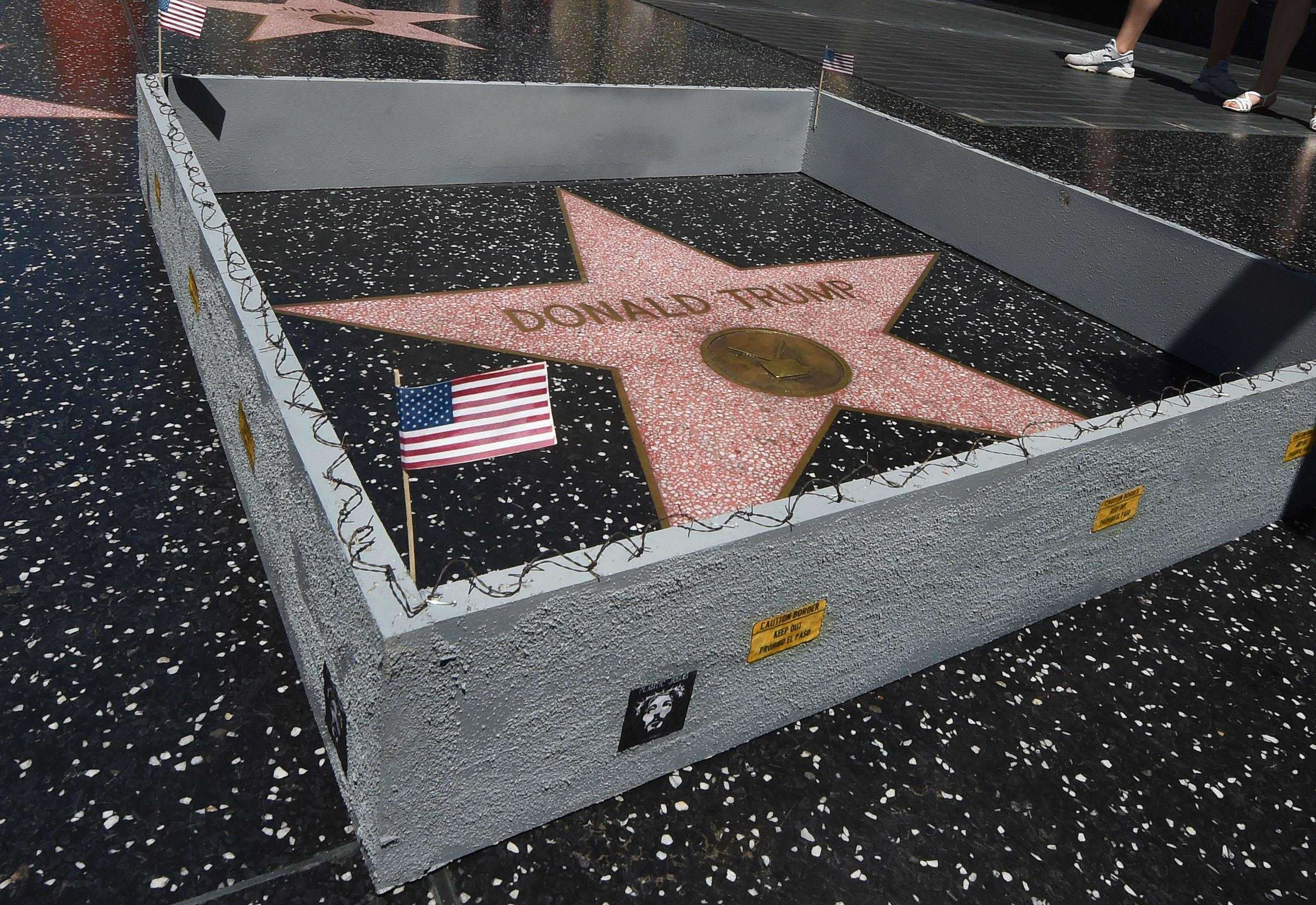 Donald Trump's Hollywood Walk of Fame star enclosed by a tiny gray fence topped with barbed wire and an American flag in one corner.
