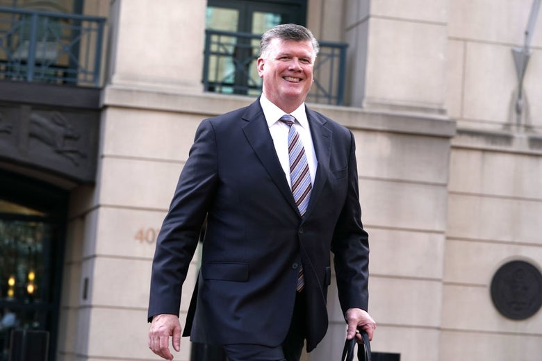 A grinning lawyer with salt-and-pepper hair and a strong jawline walks away from a courthouse.