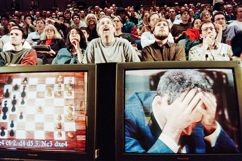 Two TV screens are seen below a sitting audience. The left screen shows a chessboard; the right shows Kasparov holding his head in his hands.