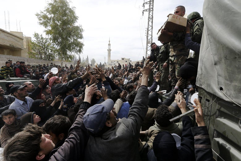 A crowd of Syrians stretching their arms up to soldiers holding boxes of food.