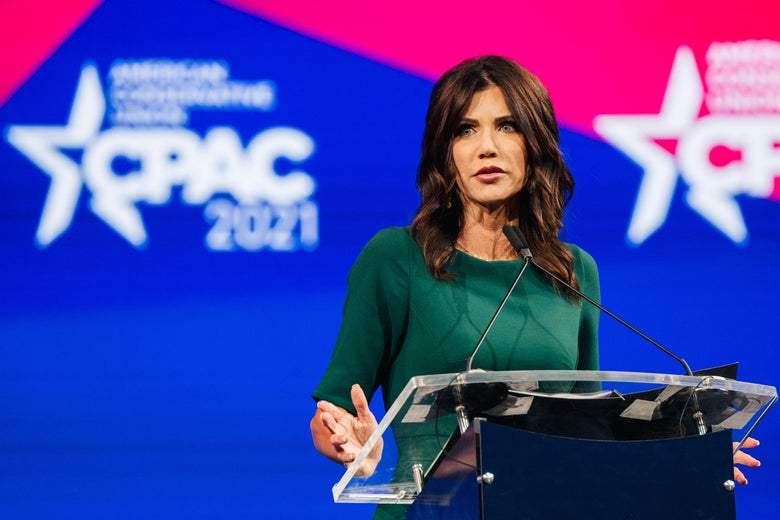 Noem speaks at a podium with the CPAC logo on a backdrop behind her
