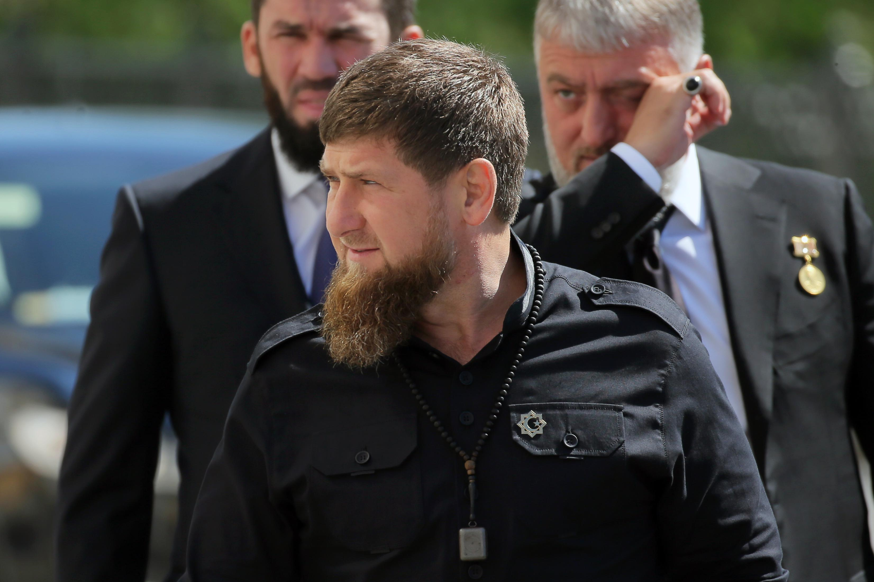 Ramzan Kadyrov, wearing a black shirt and a bushy beard, stands in front of two other men.