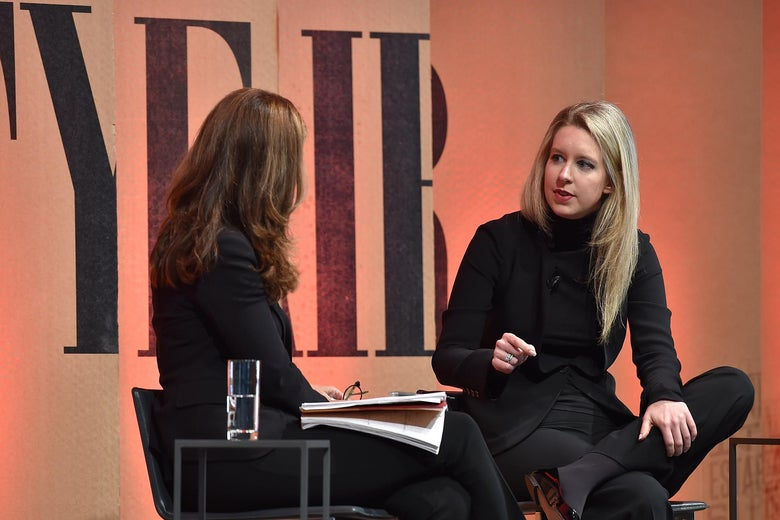 Elizabeth Holmes seated on a stage before an orange backdrop with Vanity Fair lettering