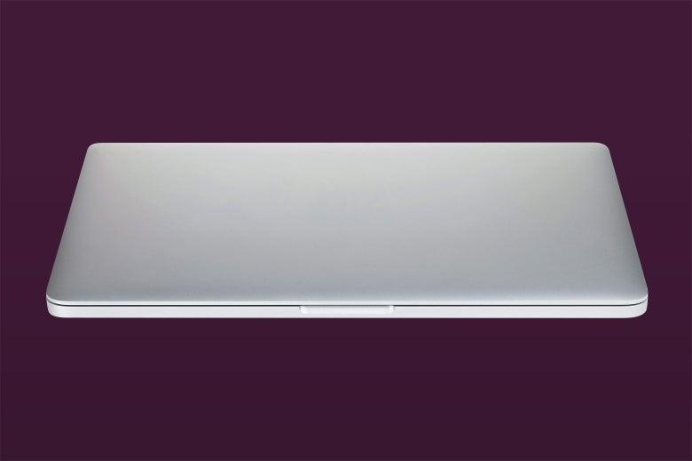A shut laptop on a dark background.