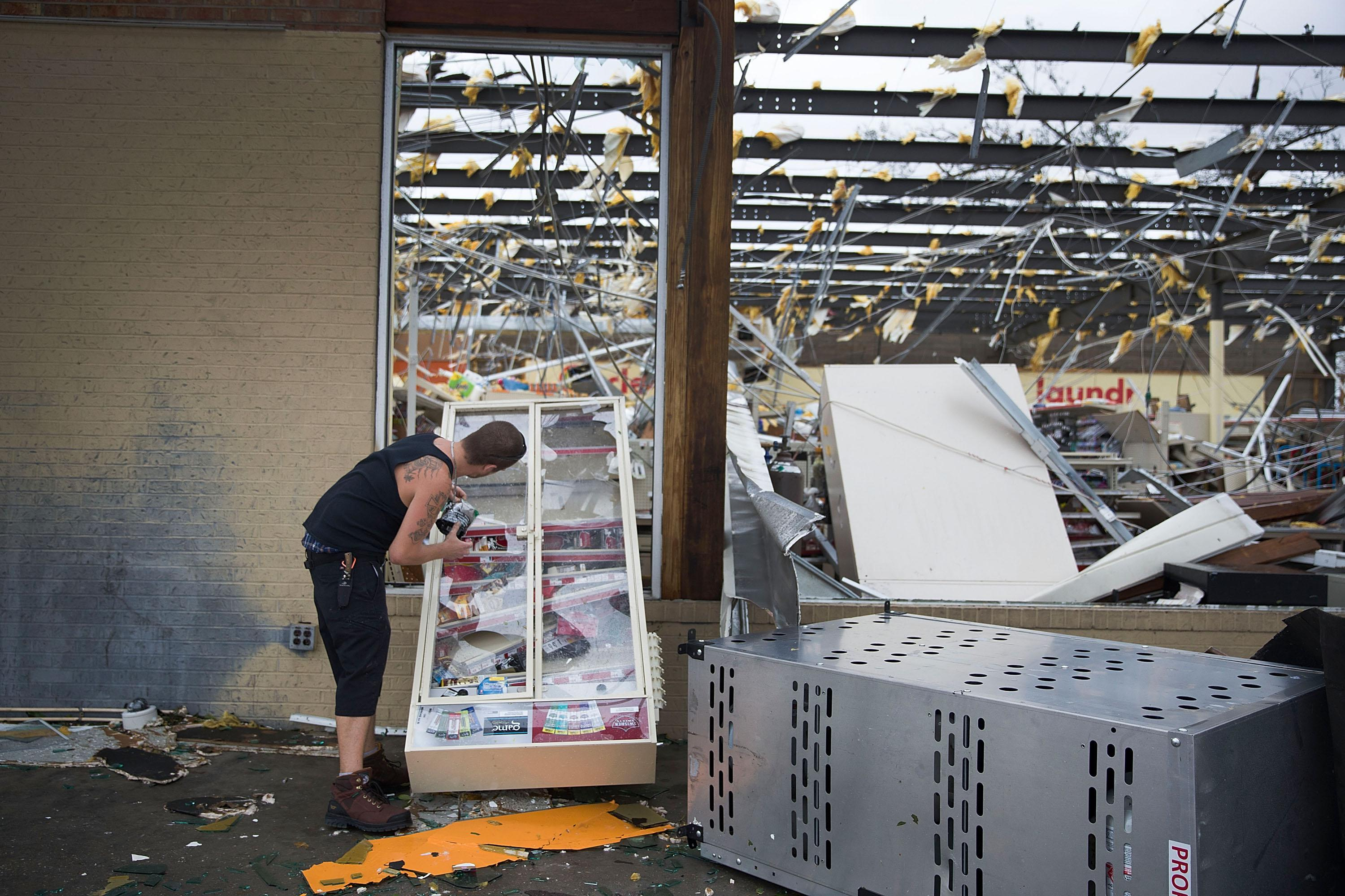 A man takes some tobacco products from a damaged store after hurricane Michael passed through the area on October 10, 2018 in Panama City, Florida.