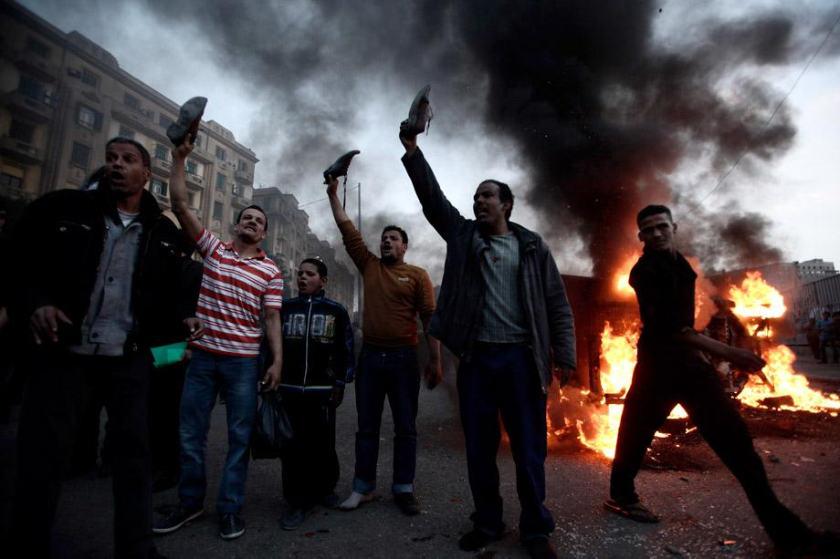 Egyptian anti-Morsi protesters hold up their shoes near a burning police vehicle in Tahrir Square during a march against a visit by U.S. Secretary of State John Kerry on March 3, 2013 in Cairo, Egypt.