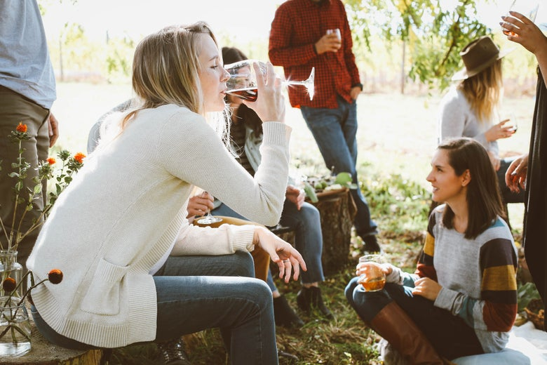 A woman drinking wine at an outdoor party.
