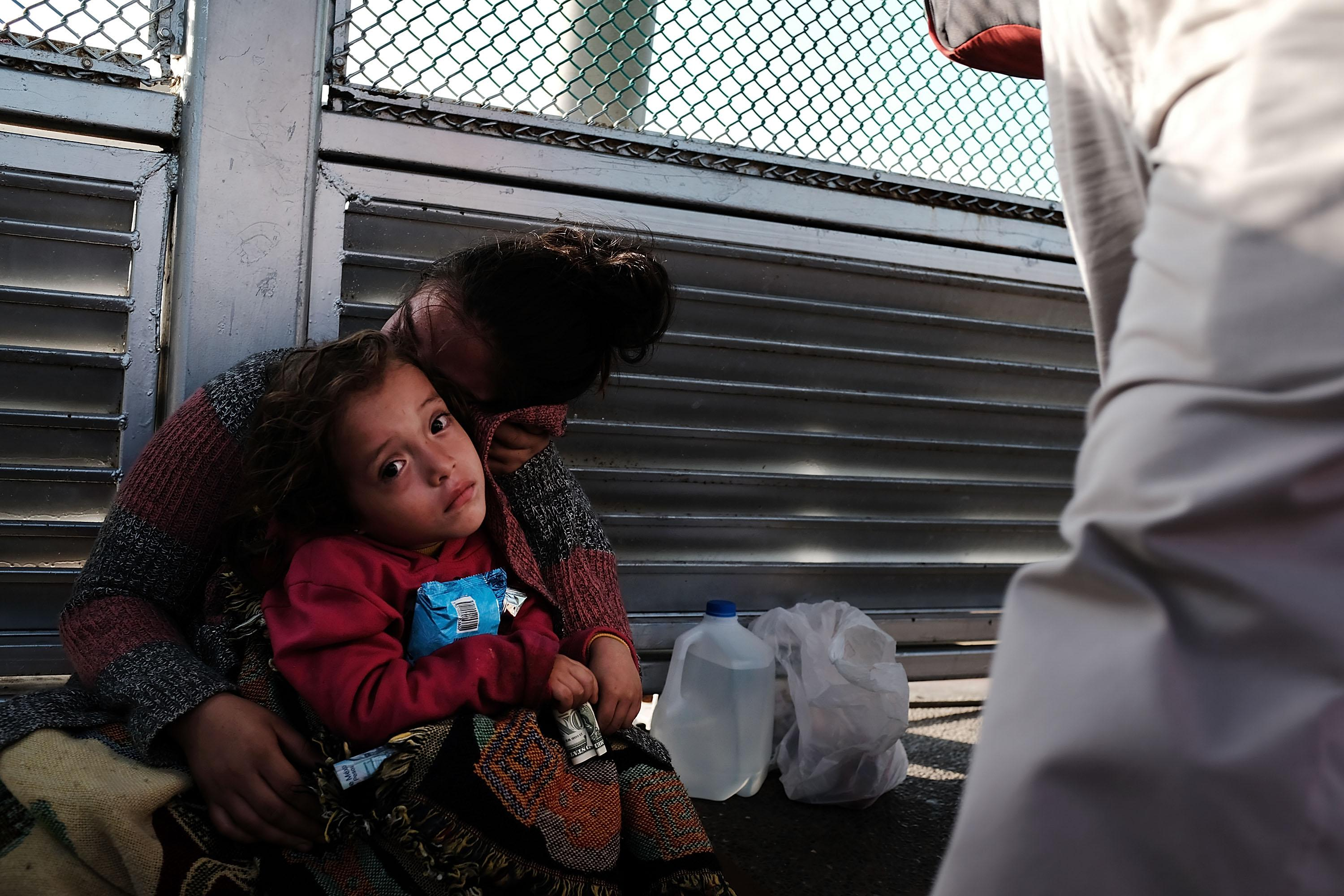 A Honduran child and her mother wait along the border bridge after being denied entry from Mexico into the U.S.
