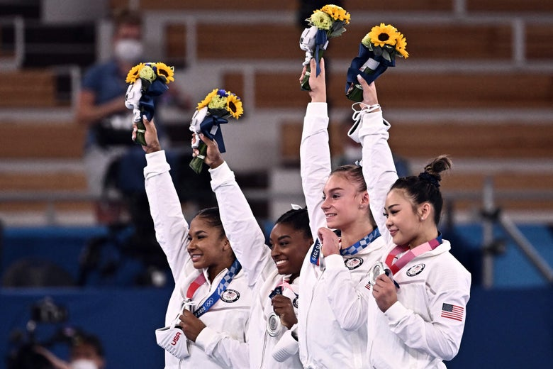 The four gymnasts stand in a row smiling on the podium. Each holds her bouquet up high with one hand and her silver medal around her neck with the other hand.