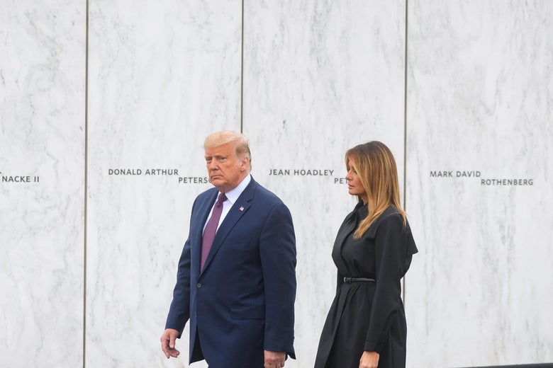 Donald and Melania Trump walking in front of a 9/11 memorial wall