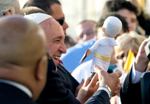 Pope Francis is given a gift as he greets well wishes after arri