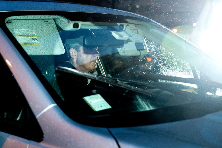 Muller is seen through the windshield of a car in the rainy pre-dawn dark.