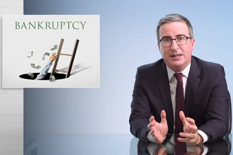 John Oliver sits at a glass desk in front of a sign reading bankruptcy.