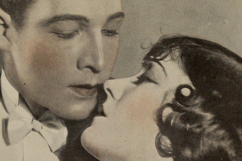 A tinted black and white photo of Rudolph Valentino and Gloria Swanson, about to kiss; Swanson is swooning.
