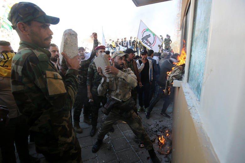 Members the Hashed al-Shaabi, a mostly Shiite network of local armed groups trained and armed by powerful neighbour Iran, smash the bullet-proof glass of the US embassy's windows in Baghdad with blocks of cement after breaching the outer wall of the diplomatic mission on December 31, 2019 to vent their anger over weekend air strikes that killed pro-Iran fighters in western Iraq.