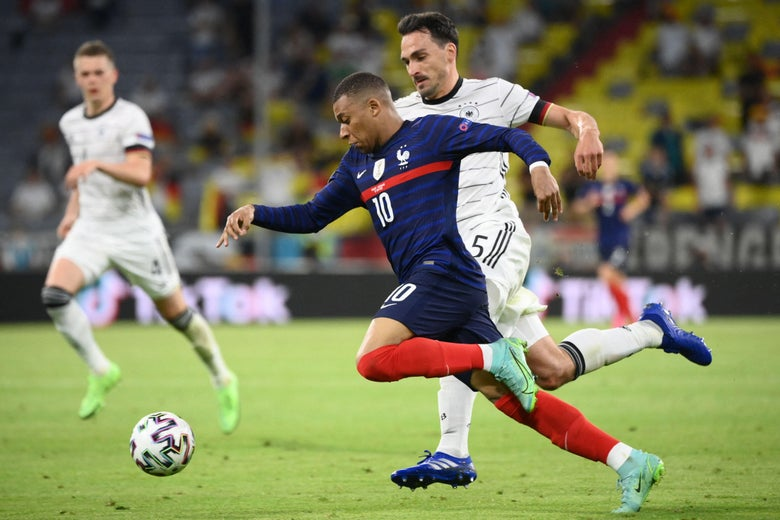 Kylian Mbappe chases the ball on the pitch against Germany, Mats Hummels chasing next to him, with another German player watching in the background