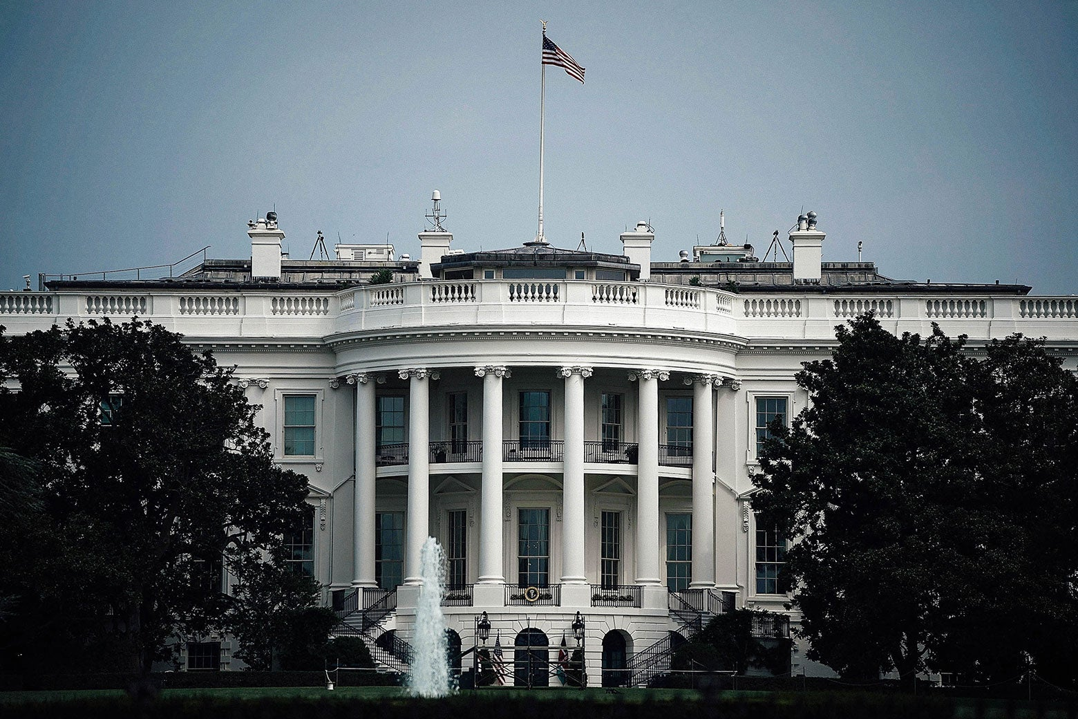 The White House with a flag on top, flown at full staff.