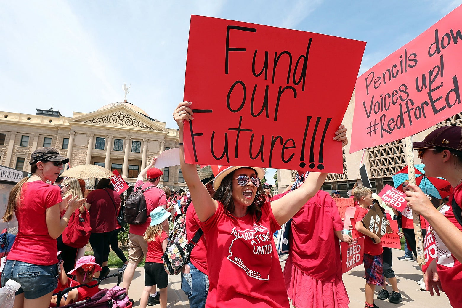 """Teachers wear red T-shirts and hold signs that say things like, """"Fund our future!!!"""""""