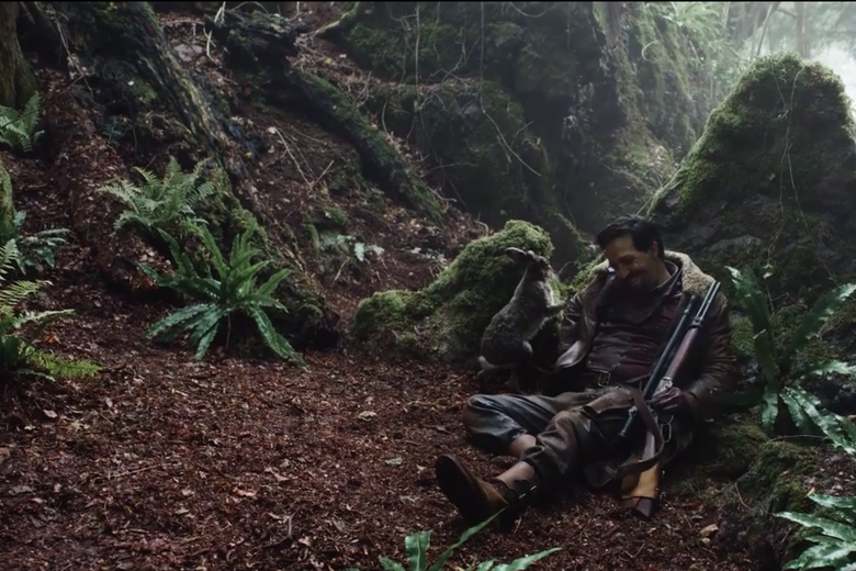 Lee Scoresby hides behind a rock with his daemon Hester in a still from His Dark Materials.