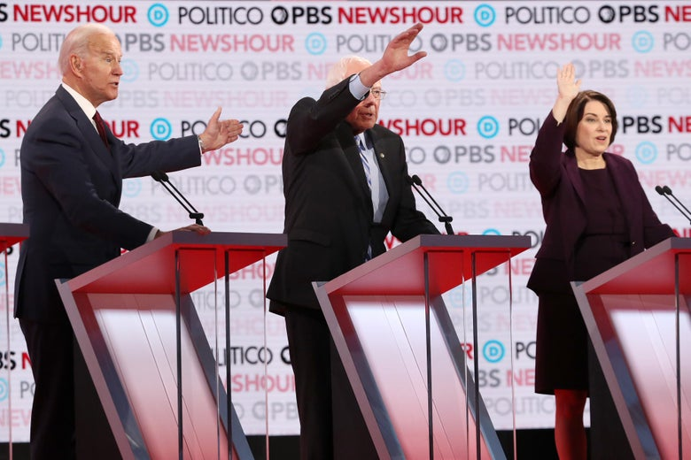 Joe Biden, Bernie Sanders, and Amy Klobuchar stand onstage behind debate podiums with arms raised to answer a question.