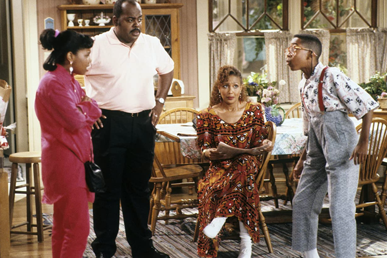 In the Winslow home's kitchen, Kellie Shanygne Williams stands with her arms crossed, facing Jaleel White, who wears big glasses and overalls. Reginald VelJohnson watches with his hands on his hips, and Telma Hopkins, seated, looks up from her newspaper.
