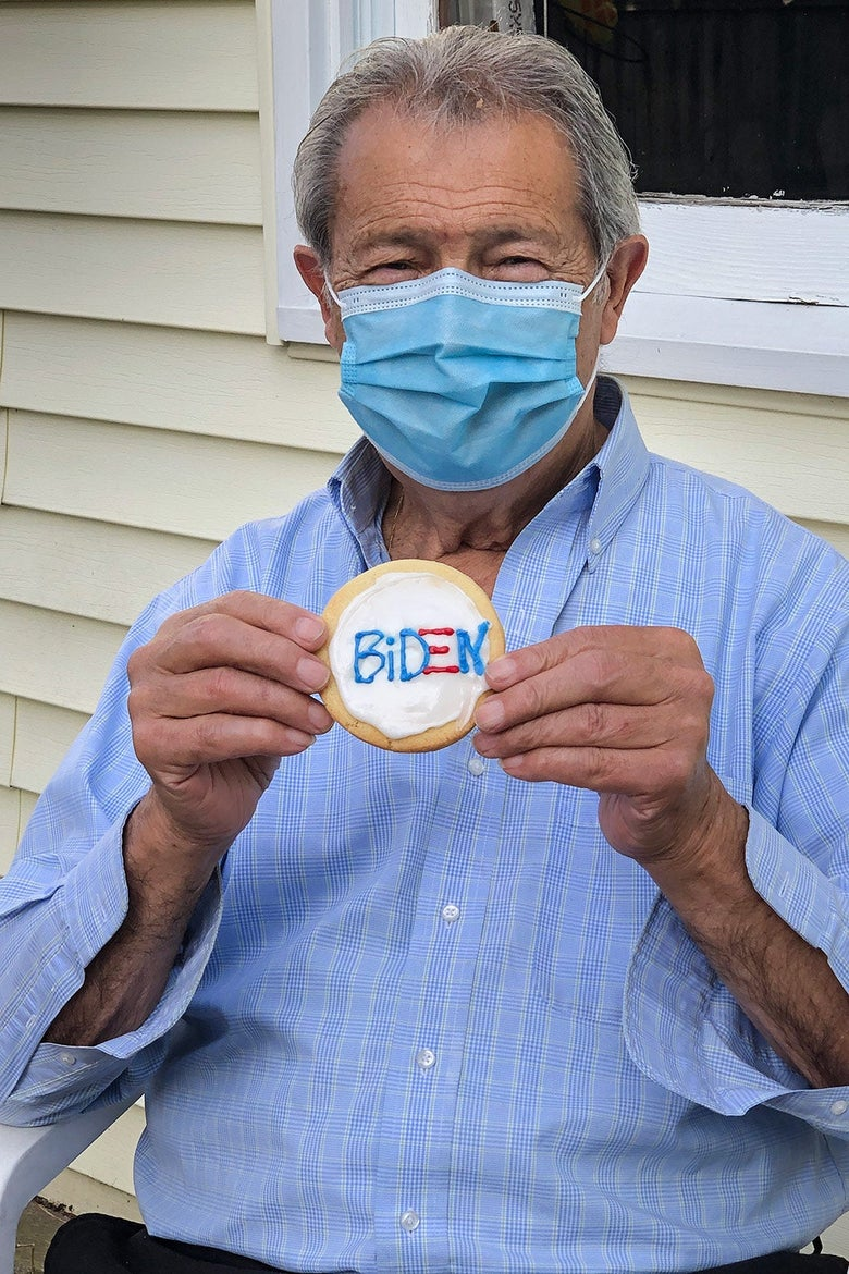 Pasquale wearing a mask and holding a cookie that says Biden on it.
