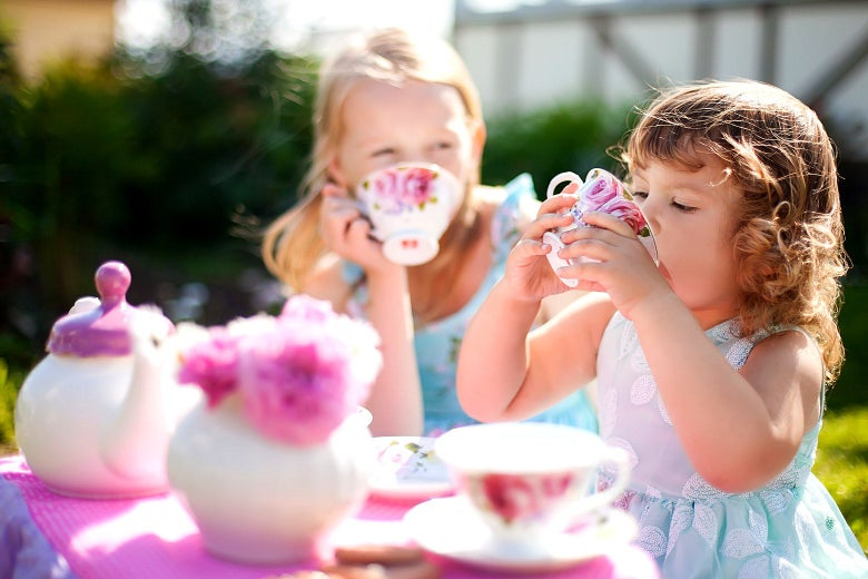Two young girls dressed like princesses have a tea party
