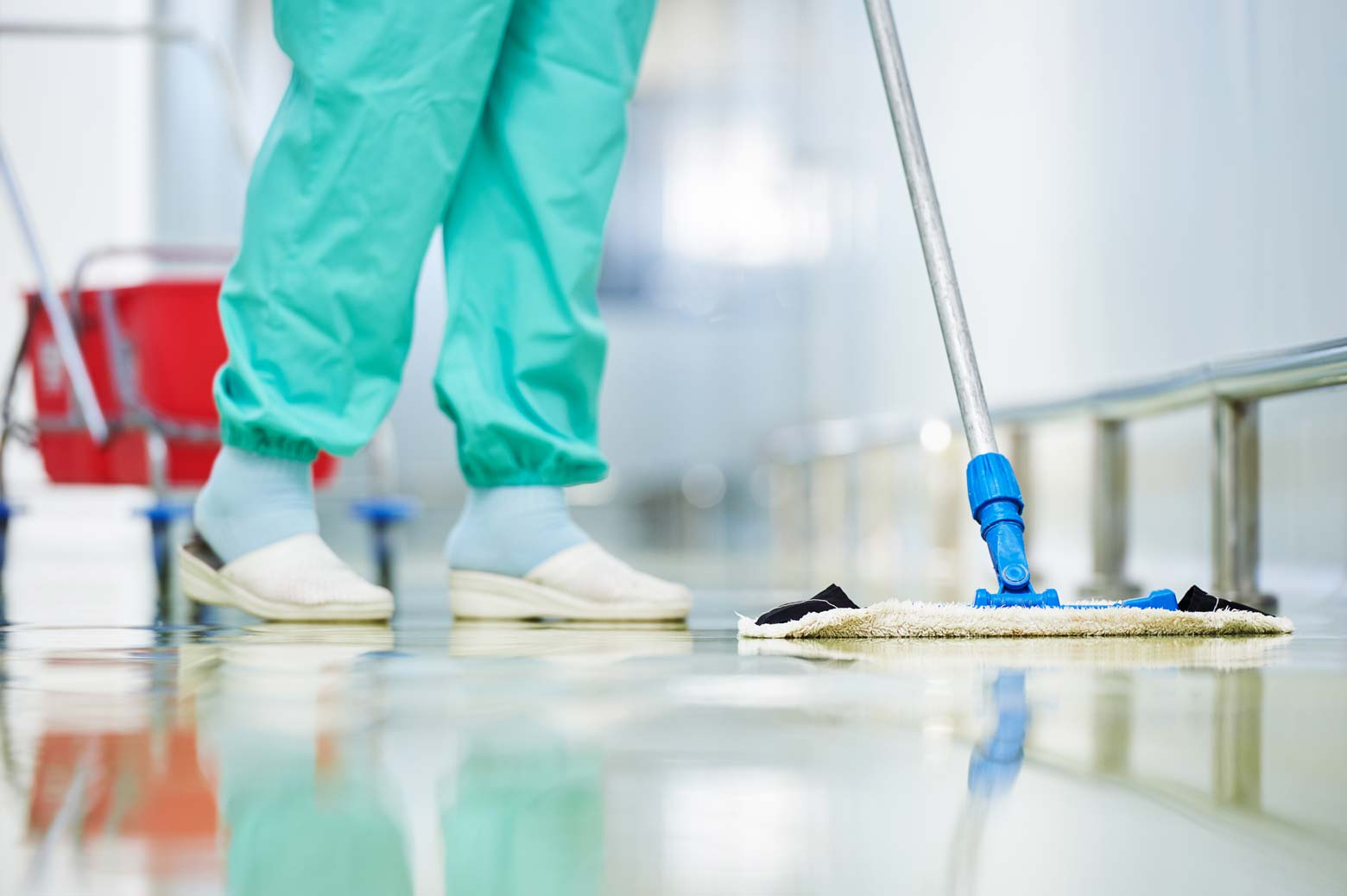 Stock image of a person wearing medical scrubs mopping the floor.