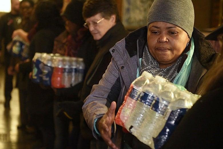 Volunteers carry cases of water bottles.