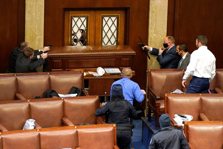 Three Capitol police officers inside the House Chamber point their gun at a door.