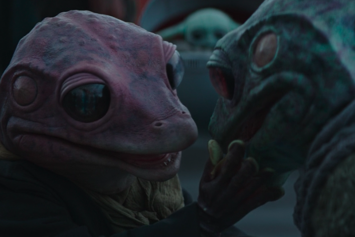A reptilian creature with large, black eyes and bumpy pink puts her hand to the cheek of a similar creature who has green skin.