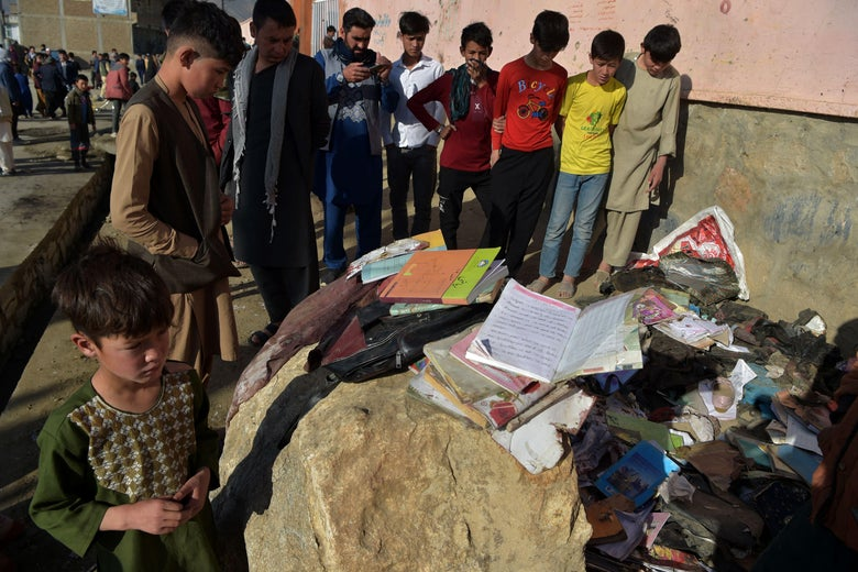 Onlookers stand next to the backpacks and books of victims following yesterday's multiple blasts outside a girls' school in Dasht-e-Barchi on the outskirts of Kabul on May 9, 2021.