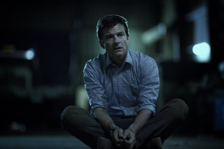 Jason Bateman sits cross-legged with his hands in front of him.