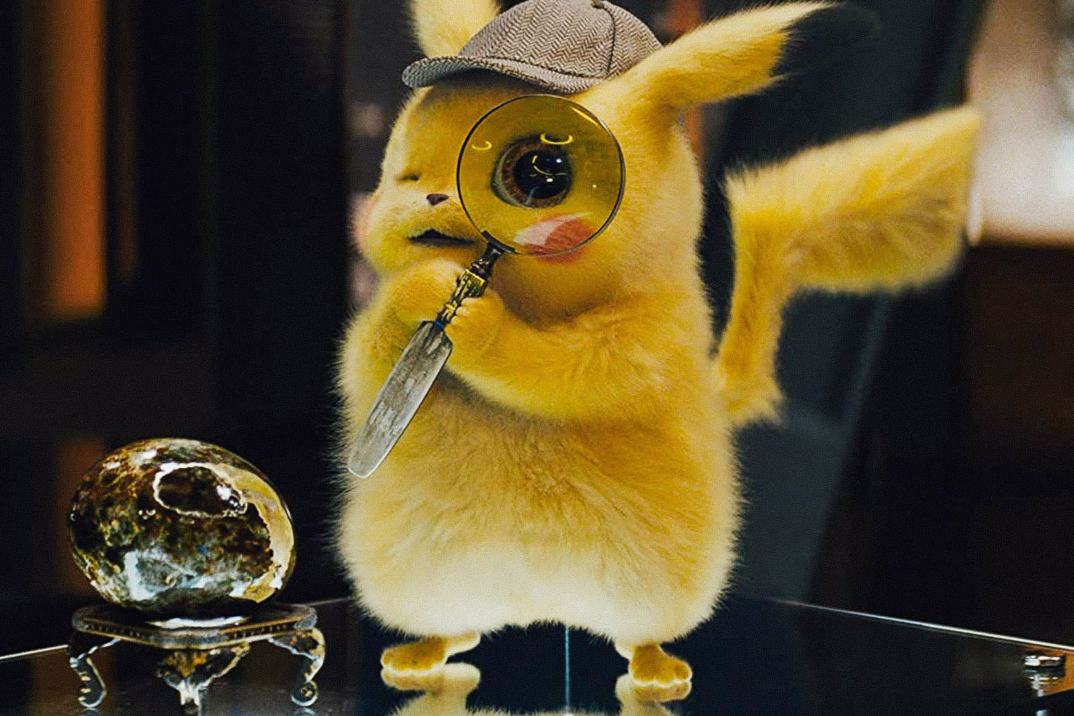 A Pikachu, voiced by Ryan Reynolds, is wearing a detective hat and holding a very large magnifying glass up to its face.